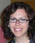 Carissa, who has brown curly hair and glasses, is smiling for a close-up headshot.