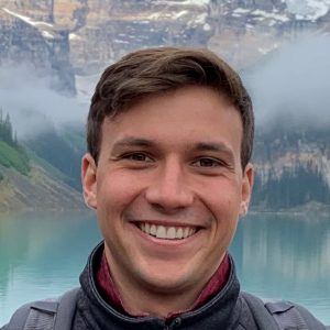 Brett, who is white and with short brown hair, smiling in front of a lake and mountains.